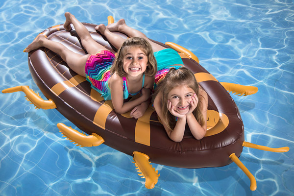 Two young girls lounging on the Cockroach Pool Float.