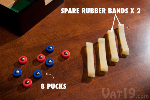 The Desktop Shuffleboard Game comes with eight pucks and four rubber bands (2 spare).
