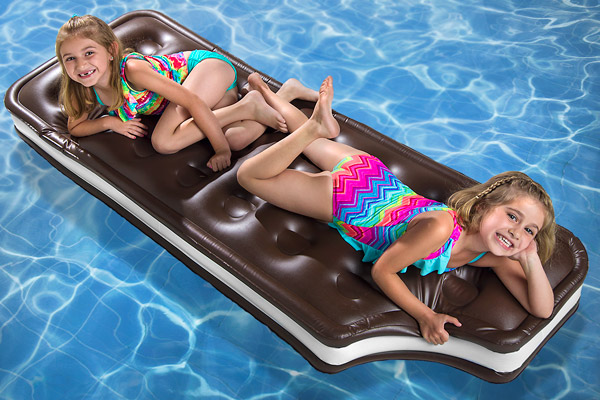 Two young girls laying on the Ice Cream Sandwich Pool Float.