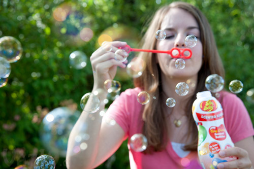 Young woman blowing Jelly Belly Scented Bubbles.