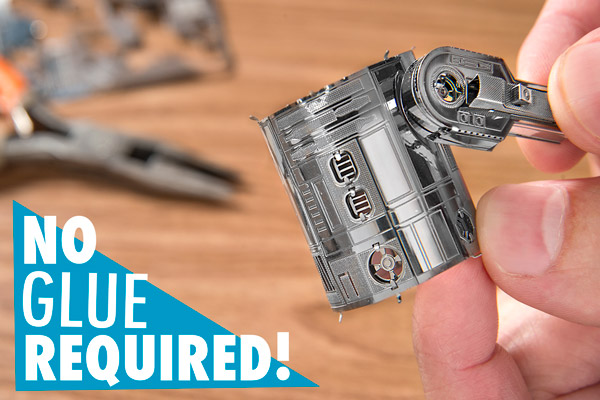 Man putting together two pieces of the R2-D2 Metal Earth 3D Model.