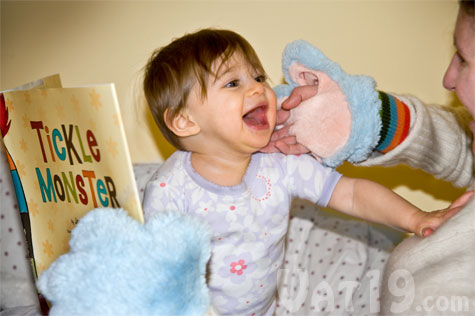 Child being tickled while reading Tickle Monster Laughter Kit