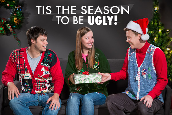 Three adults enjoying a quiet evening at home in their delightfully tacky Christmas sweaters.