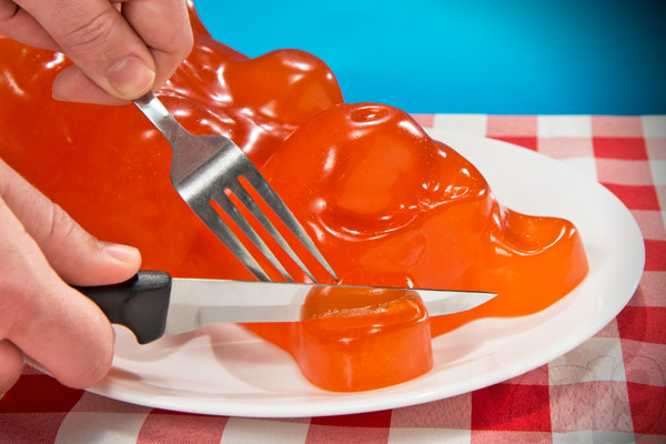 Eating the World's Largest Gummy Bear with a knife and fork.