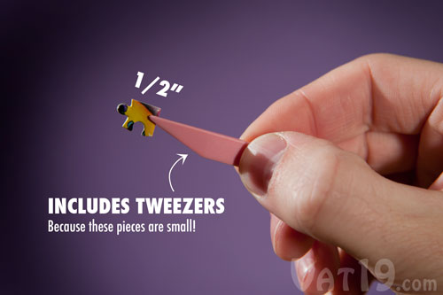 A piece from the World's Smallest Jigsaw Puzzle being held by a pair of tweezers.